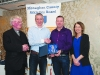 Chairman of the Monaghan County Athletics Board, Alan Clarke, 2nd from left, making the presentation to Damien Barry, Monaghan Phoenix AC. Also included are Fr Paudge Corrigan and Rose Lambe. ©Rory Geary/The Northern Standard