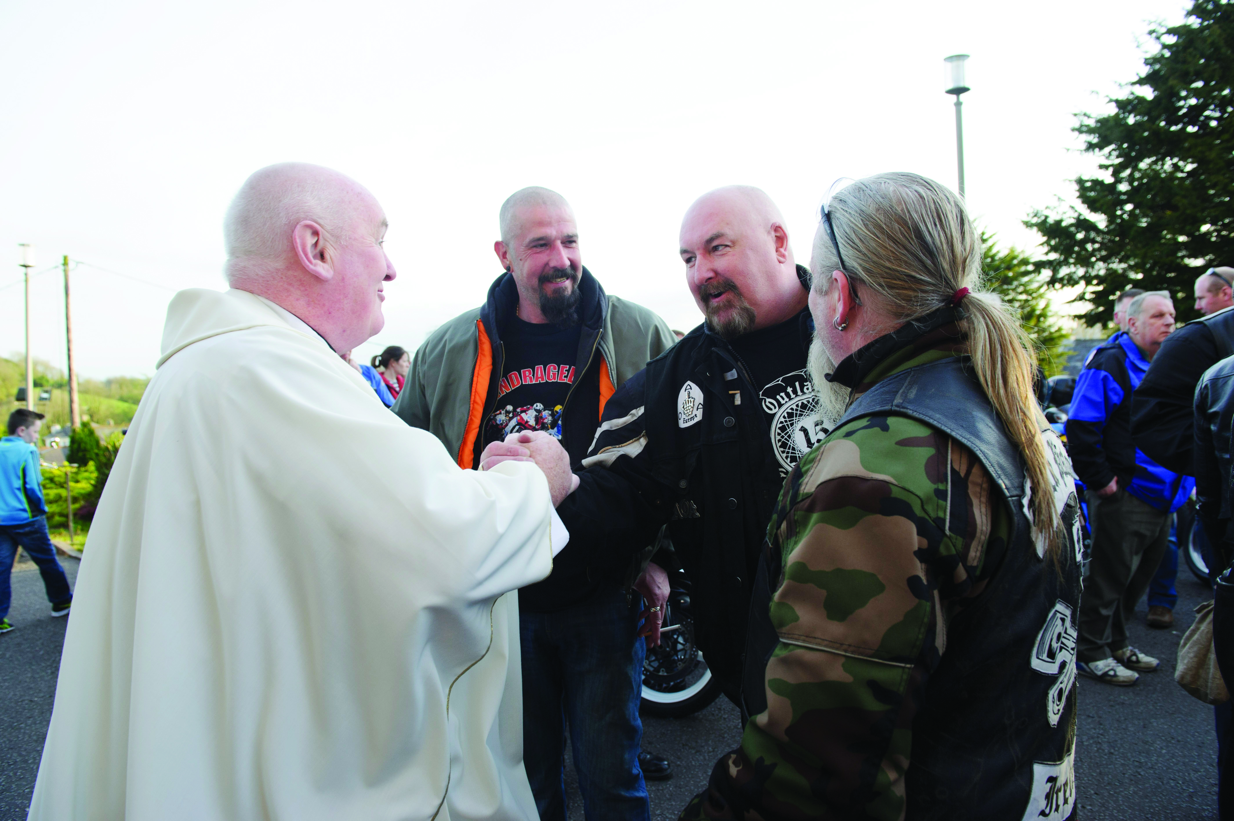 Fr John  Kierans is welcomed by some of the motorbike club members at the Gone But Not Forgotten Bikers Mass. ©Rory Geary/The Northern Standard
