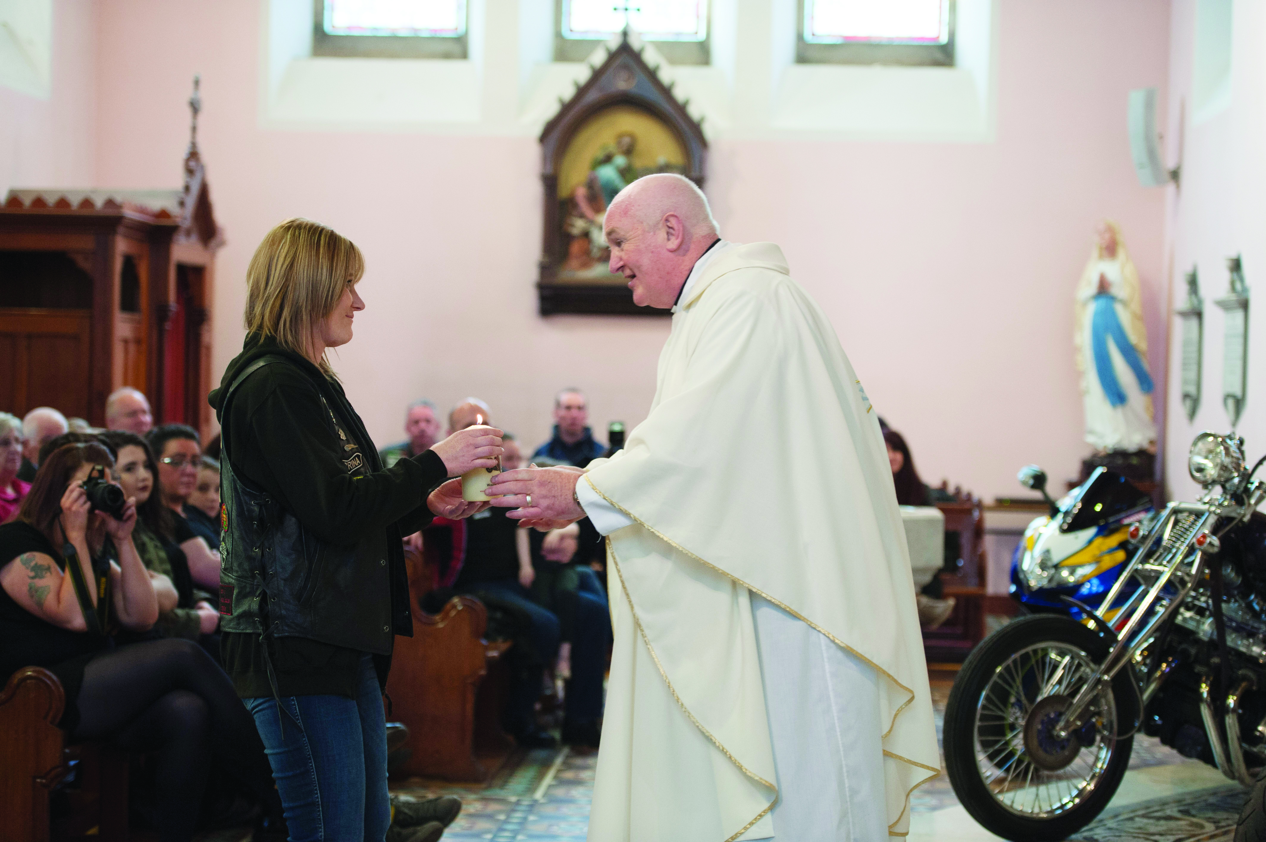 Fr John Kierans receiving a candle in memory of a deceased biker during the mass. ©Rory Geary/The Northern Standard