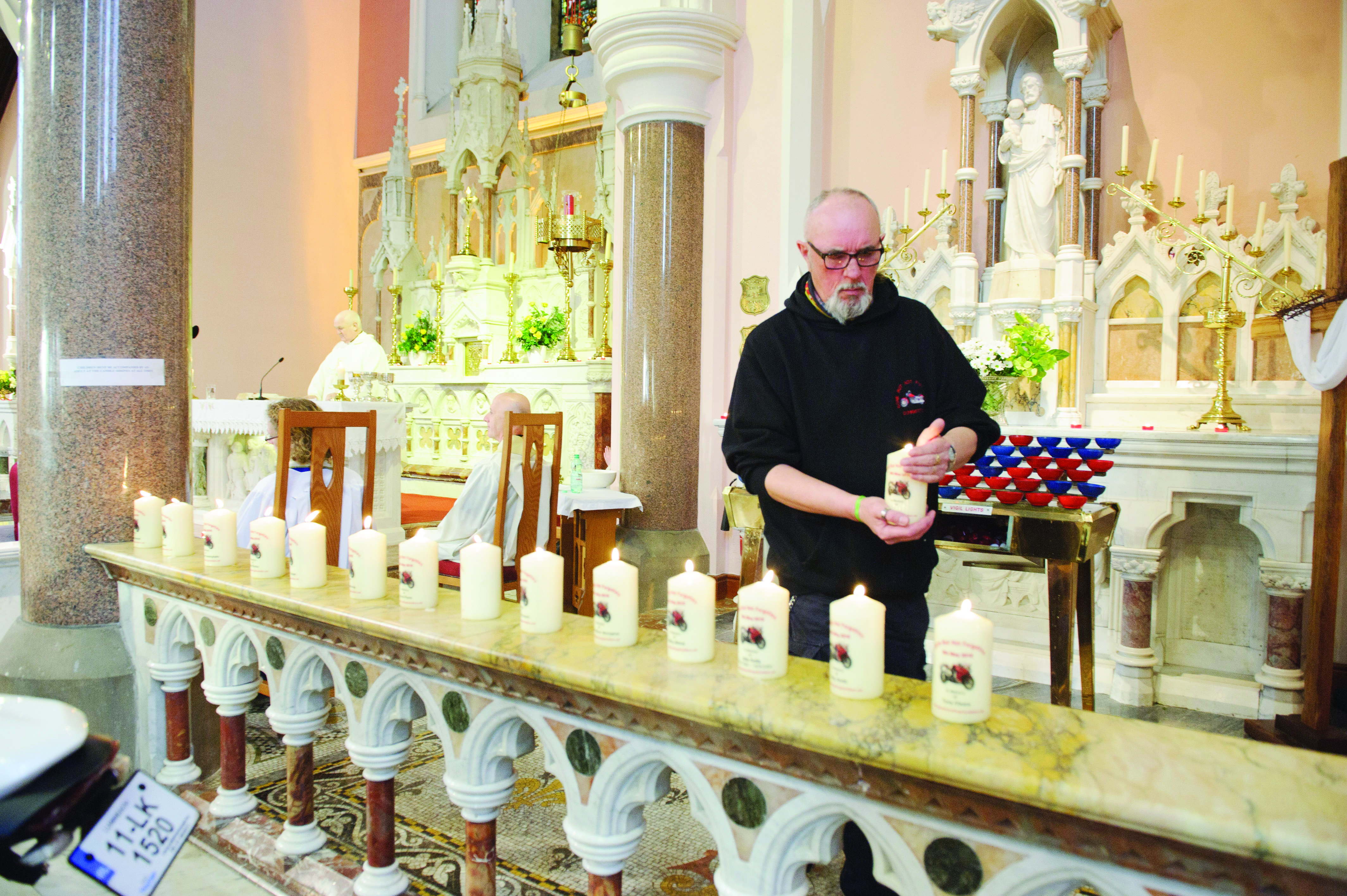 Vinny West placing some of the candles that were lit in memory of deceased bikers on the alter during the Gone But Not Forgotten Bikers Mass. ©Rory Geary/The Northern Standard