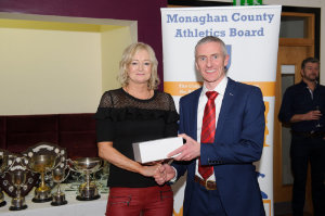 Alan Clarke, chairman of the Monaghan County Athletics Board, making the presentation to Michelle Reinhart-McCabe, Clones AC. ©Rory Geary/The Northern Standard