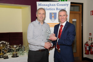 Brian Peppard, left, Monaghan Phoenix AC, accepting the award on behalf of Macartan Kieran, from Alan Clarke, chairman of the Monaghan County Athletics Board. ©Rory Geary/The Northern Standard