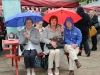 Taking shelter from the rain during the Monaghan Canada Day celebrations were (L-R) Peggy McElwaine, Violet and Mark McCabe. ©Rory Geary/The Northern Standard