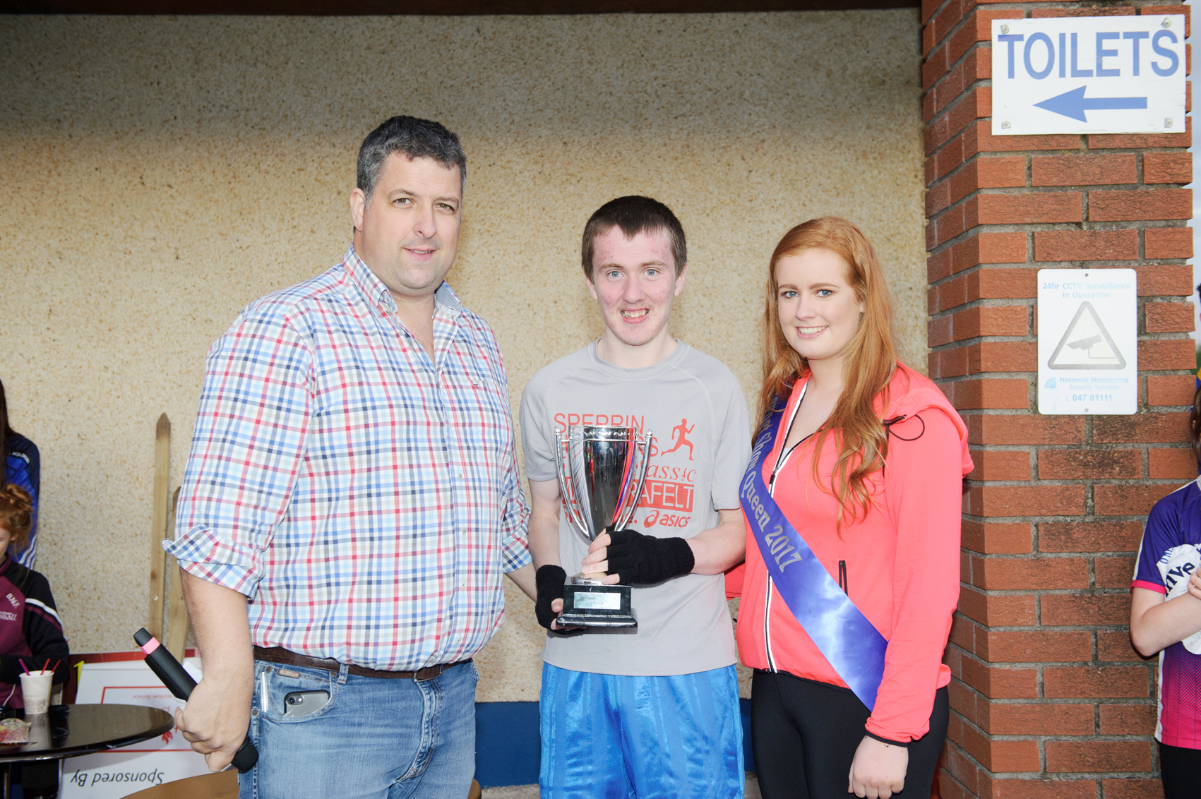 Shane Brady, centre, Clones AC, being presented with the cup for winning The Ned Run by Stephen McKenna and Shauna McAree, Tydavnet Show Queen. ©Rory Geary/The Northern Standard